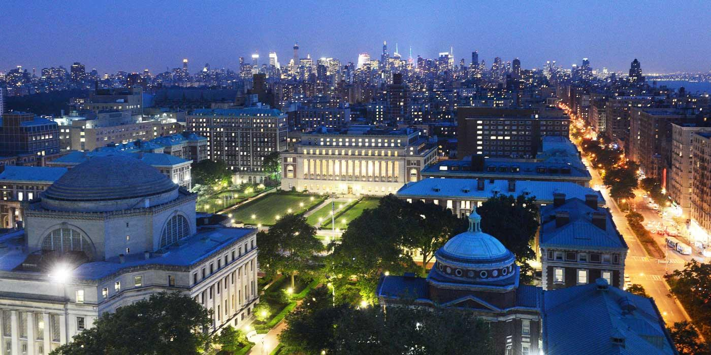 Aerial photograph of Morningside campus at night, with the NYC skyline in the background