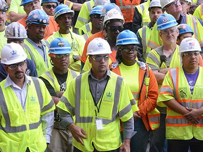 diverse construction workers standing in hard-hats and neon yellow work vests